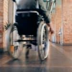 Rollstuhlfahrer fährt einen Korridor entlang