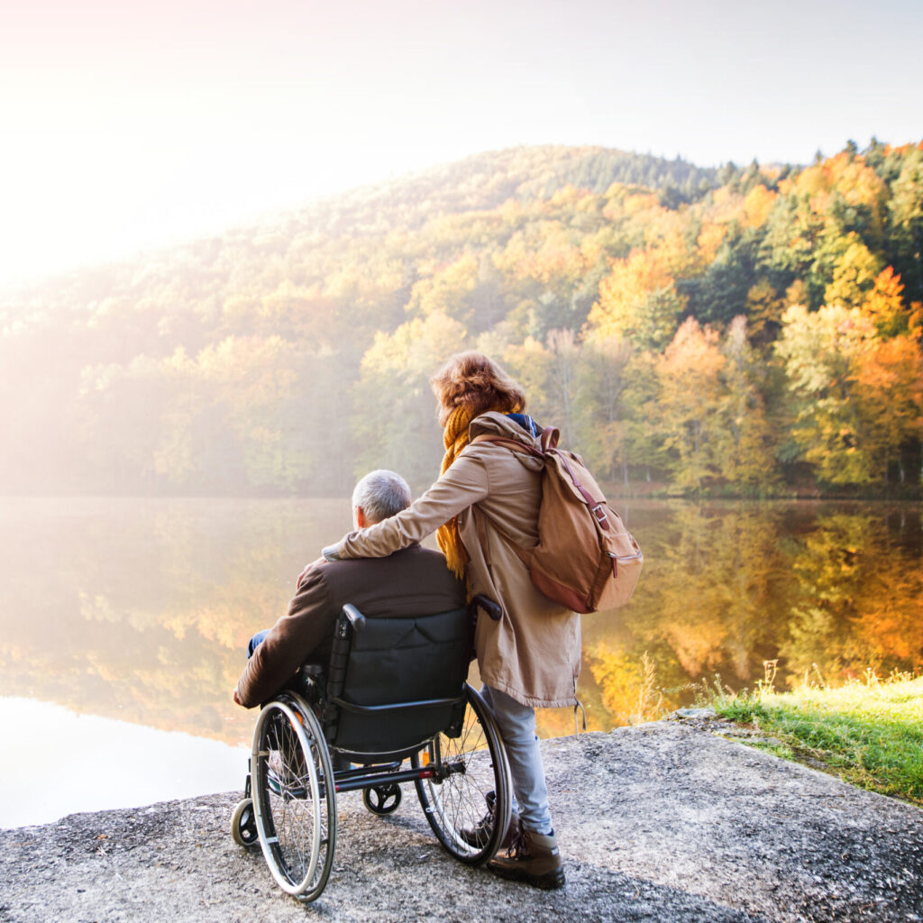 Man in wheelchair with partner, standy by a lake in autumn